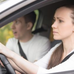 Failed Driving test. Young serious inexperienced woman driving a car in alert, worried instructor man sitting aside and looking nervous at the road, dangerous situation